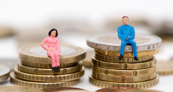 Die Figuren eines Mannes und einer Frau sitzen auf ungleichen Stapeln aus Geldmünzen. Foto: picture alliance / dpa Themendienst / Andrea Warnecke.