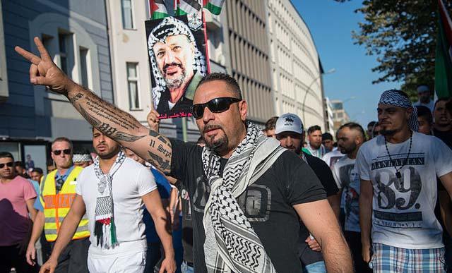 """Antisemitische Demonstration in Berlin am 17. Juli 2014: Der Teilnehmer mit Palästinensertuch hat """"88"""" am rechten Unterarm eintätowiert - ein Nazi-Zahlencode für den Hitlergruß, darüber ein Lob auf die Palästinenser, die sich """"als einzige … gegen den Zionisten wehren"""""""