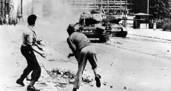Demonstranten werfen Steine auf einen russischen T-34 Panzer in Ost-Berlin am 17. Juni 1953. Foto: picture alliance / AP Photo.